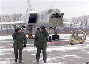 """Two Ukrainian air force officers walk away from their decommissioned Tupolev Tu-22M-3, """"Backfire"""" strategic, nuclear-capable bomber in 1996."""